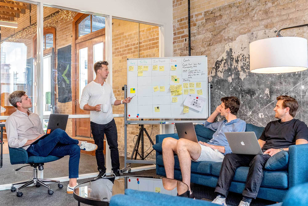 four-men-in-a-meeting-looking-at-whiteboard-(1)